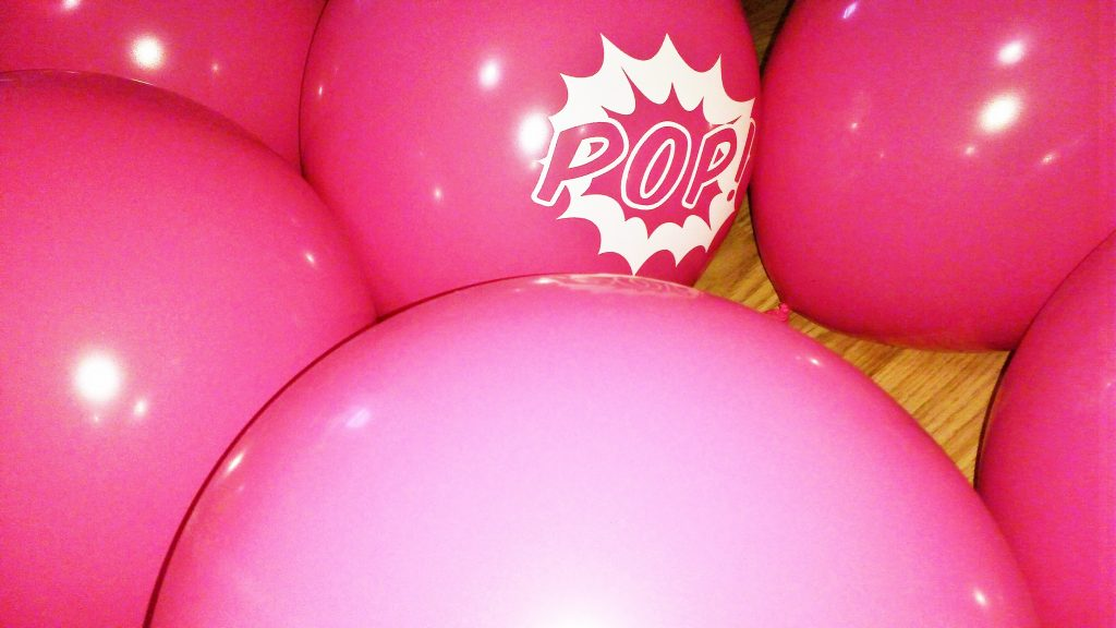 superhero party pink balloons pop