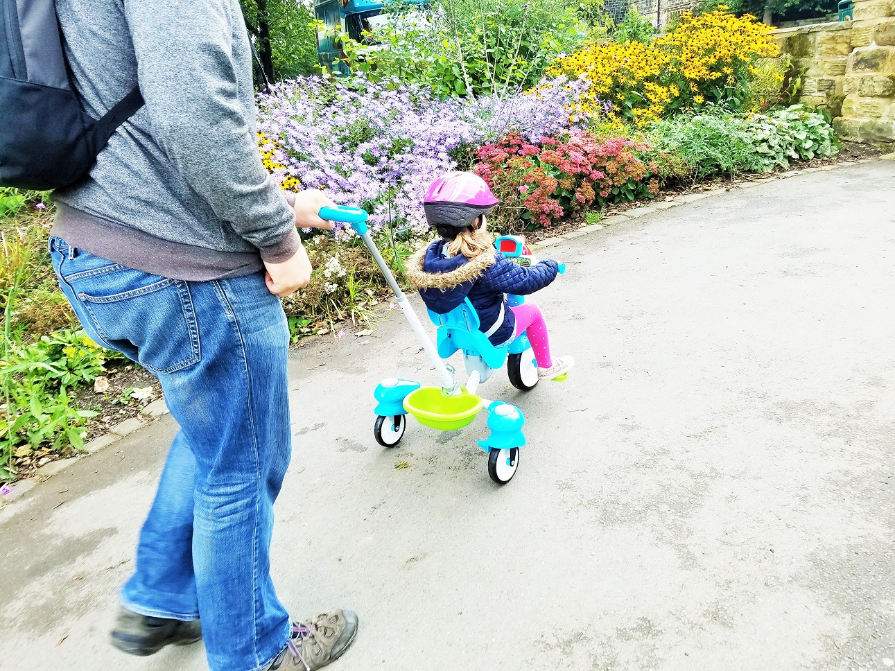 vtech trike next to some flowers