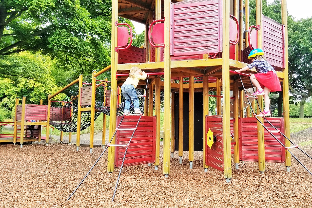 Siblings playing in the playground, climbing towards the same goal