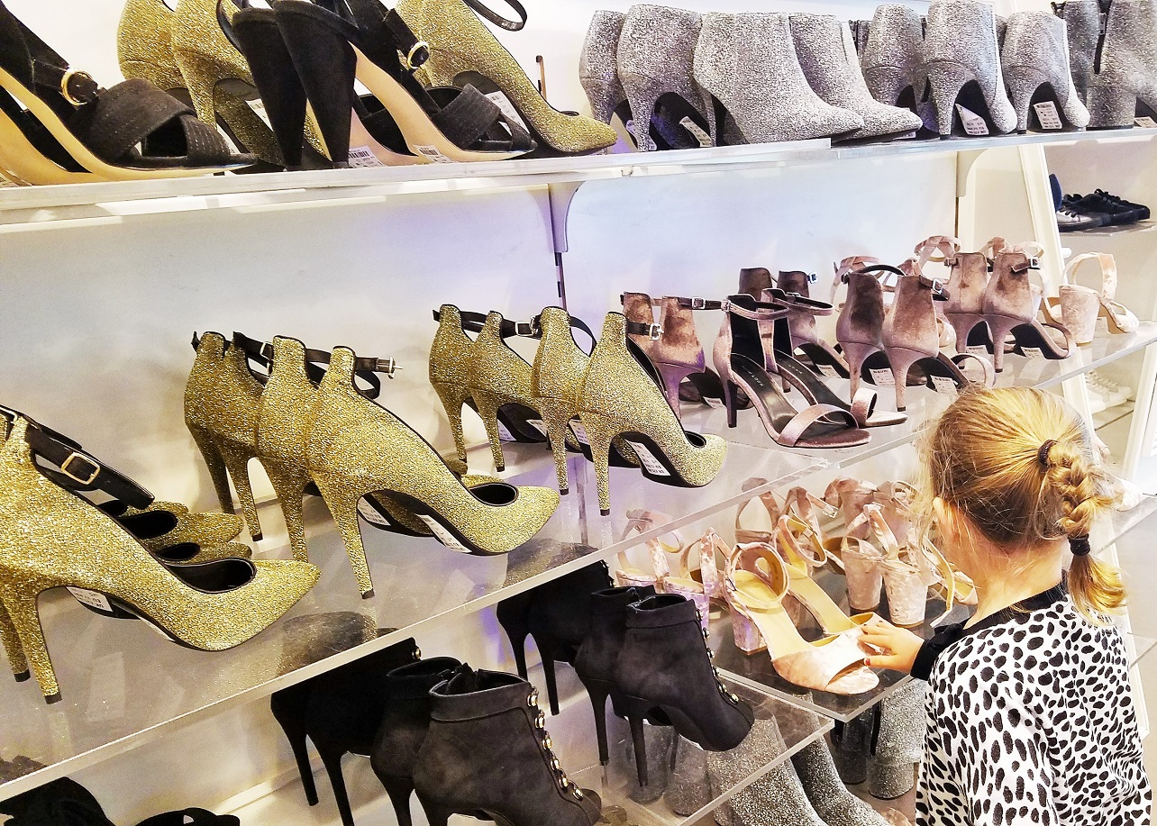 Childhood anxiety - young child looking at sparkly shoes at the shops - too many decisions
