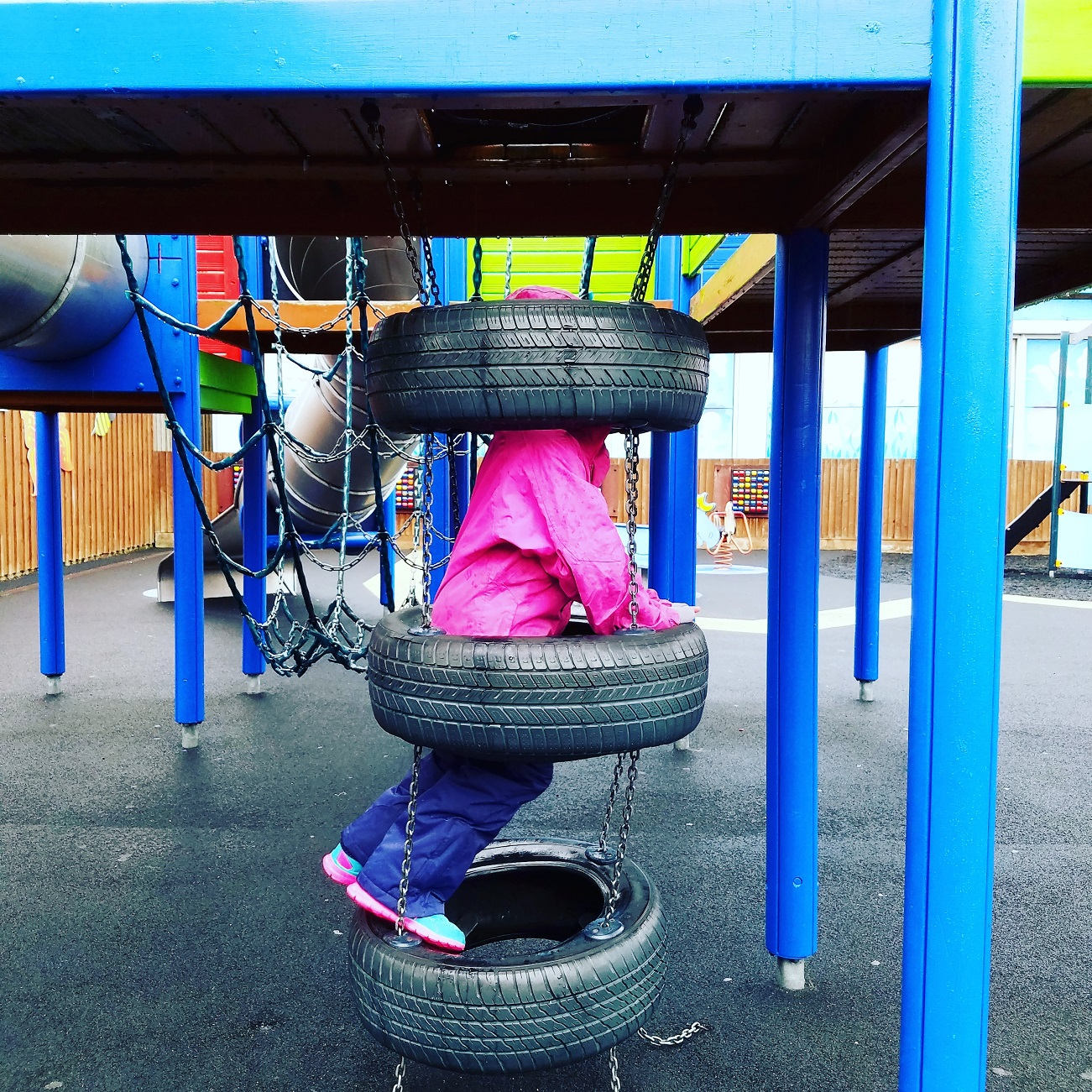 average child - climbing frame at playground tyres