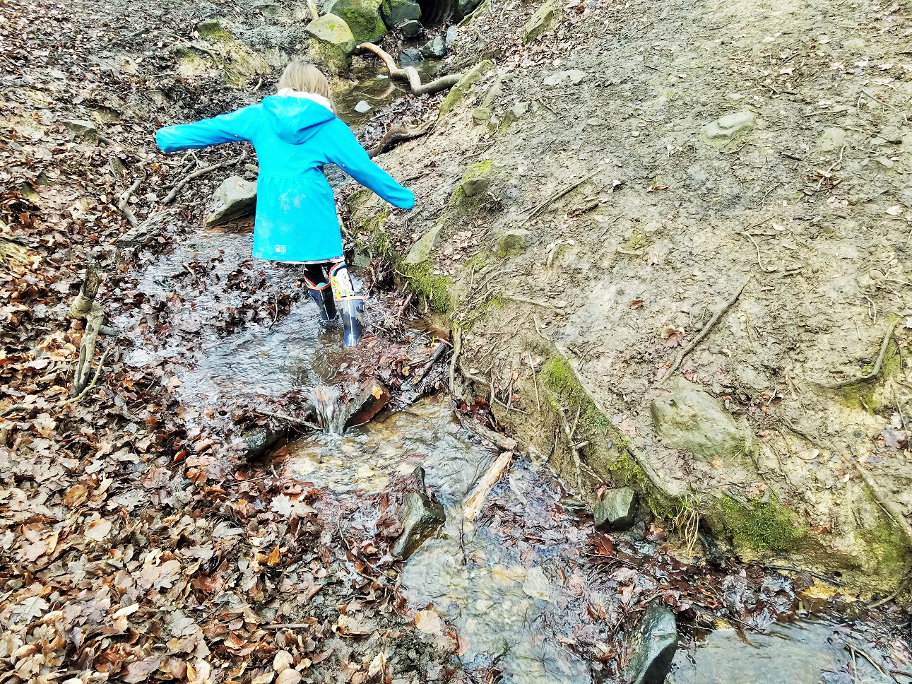 stay at home mum need a break - small child on an adventure walking in a muddy stream