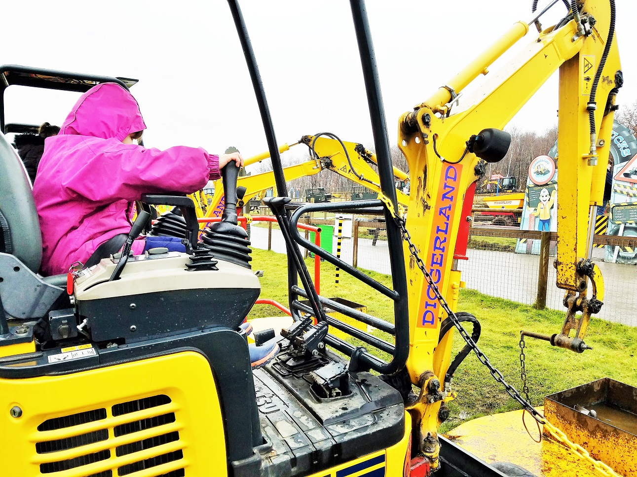 Diggerland in the rain - child operating digger arm at diggerland