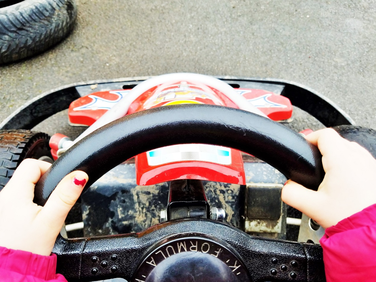 Diggerland in the rain - child with her hands on a go-kart steering wheel