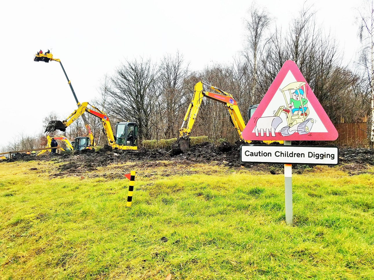 "Diggerland in the rain - sign saying ""caution children digging"""