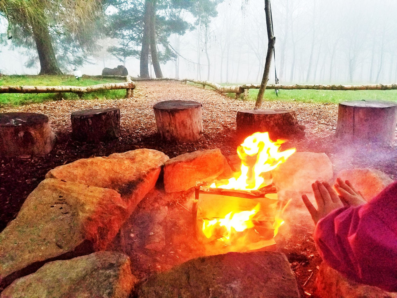 Child warming hands over a bonfire - family glamping site near Beverley called North Star Club