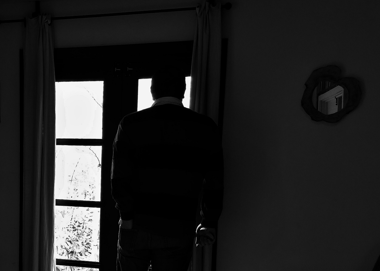 Love is an action - man stood by window in a dark room