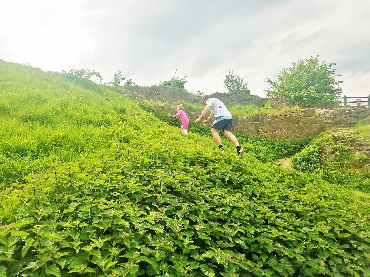 dictator mummy - child and father climbing a steep hill. Father holds hands out to steady child