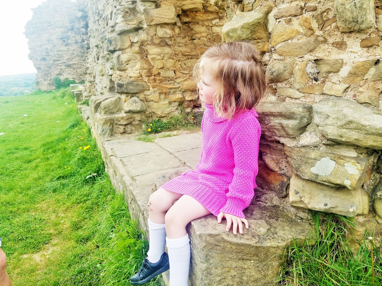 Dictator mummy - child sitting on an old castle wall