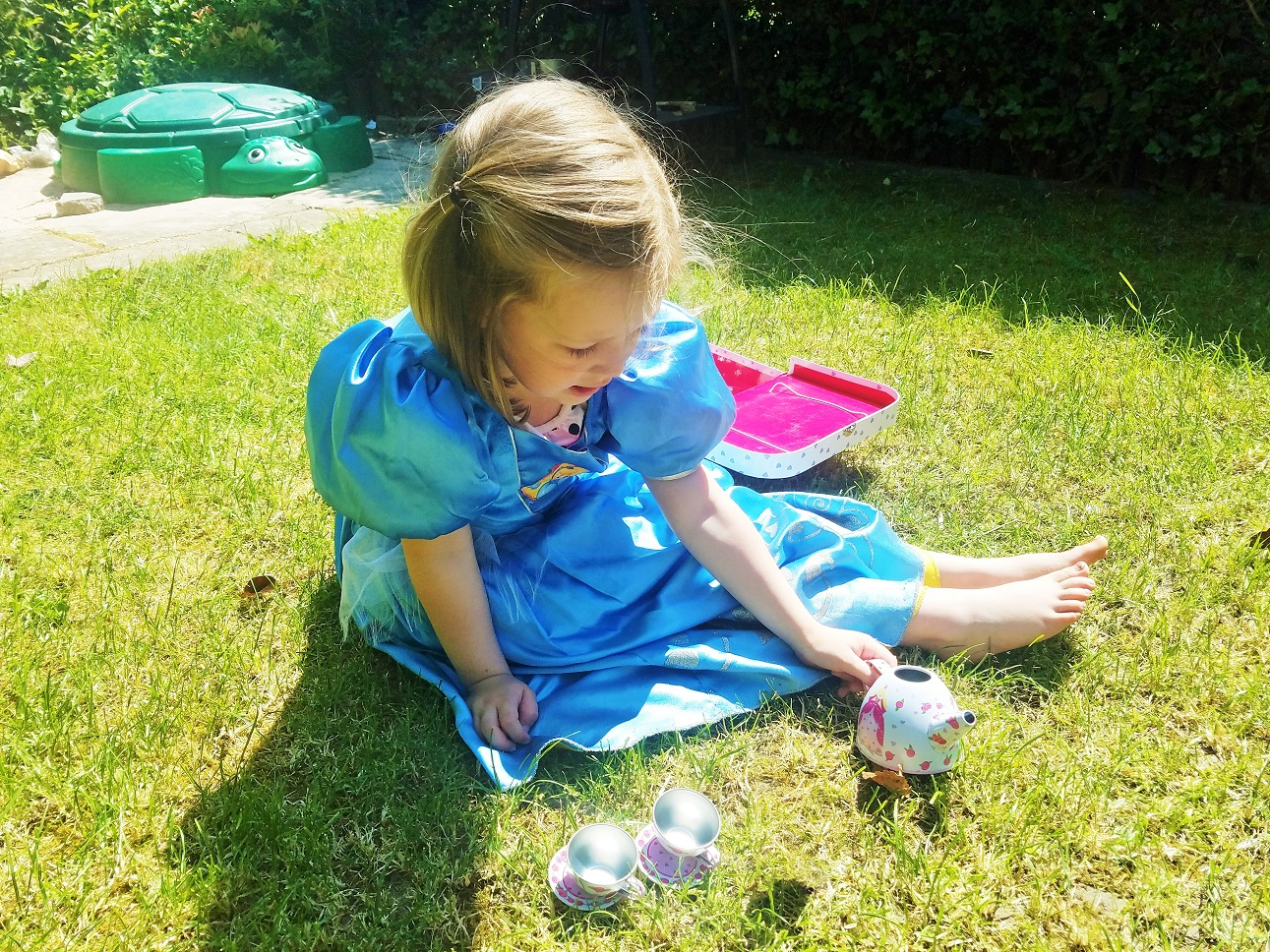 Mums With L Plates Facebook Group - child in a princess dress having a tea party in the garden