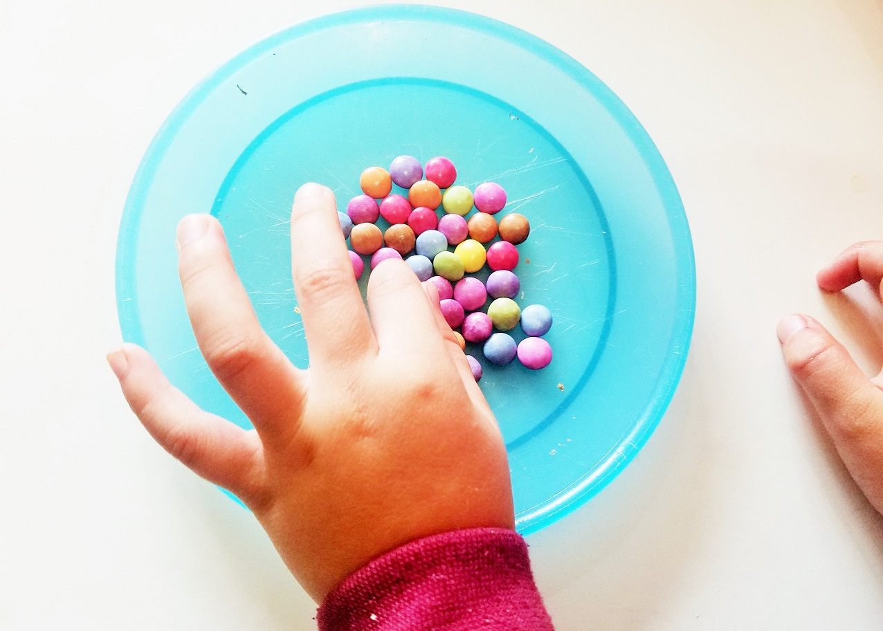 Empathic parenting and the art of listening - child picking up some colourful sweets