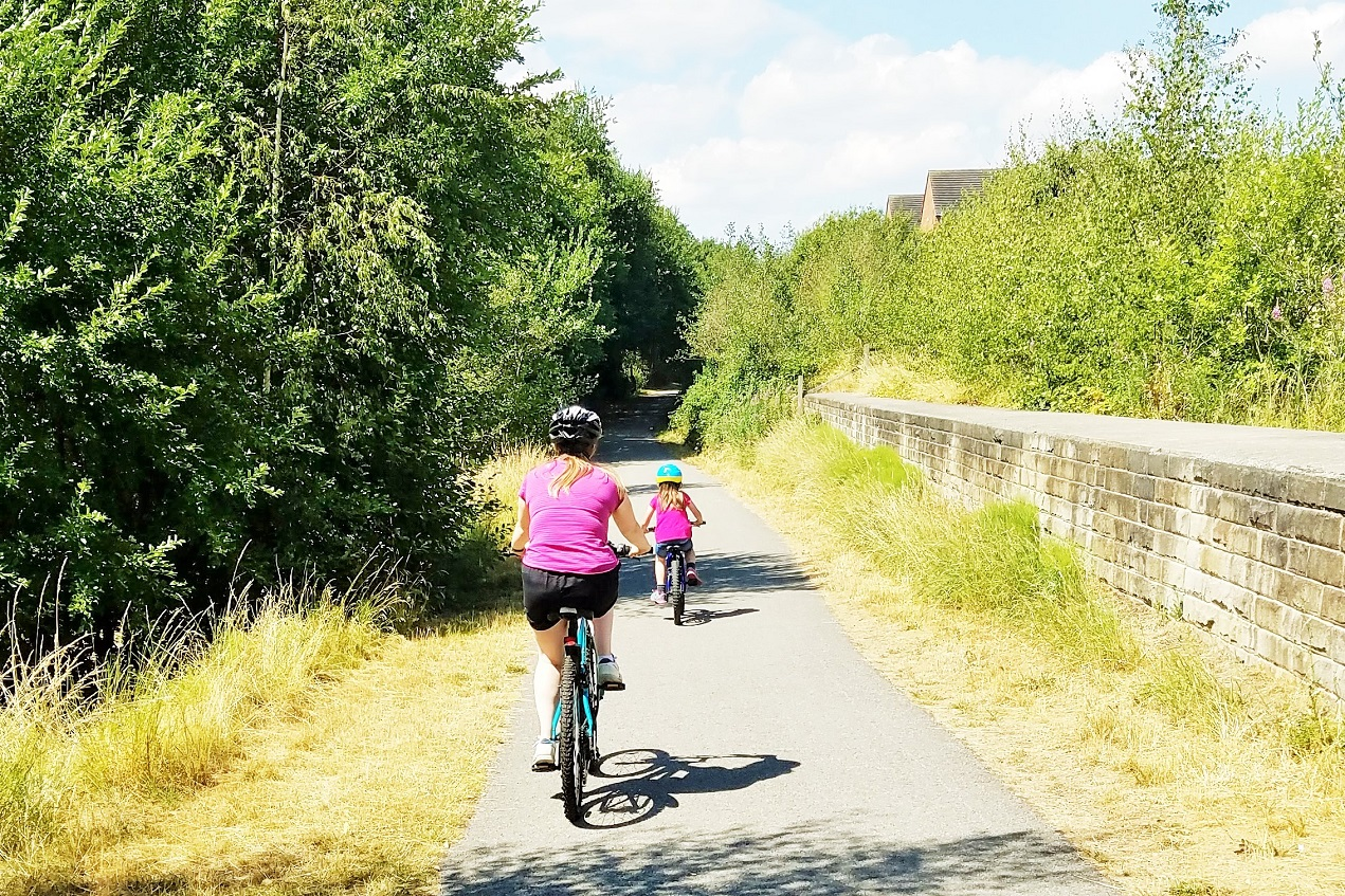 The importance of cause and effect in gentle parenting - mum cycling with daughter