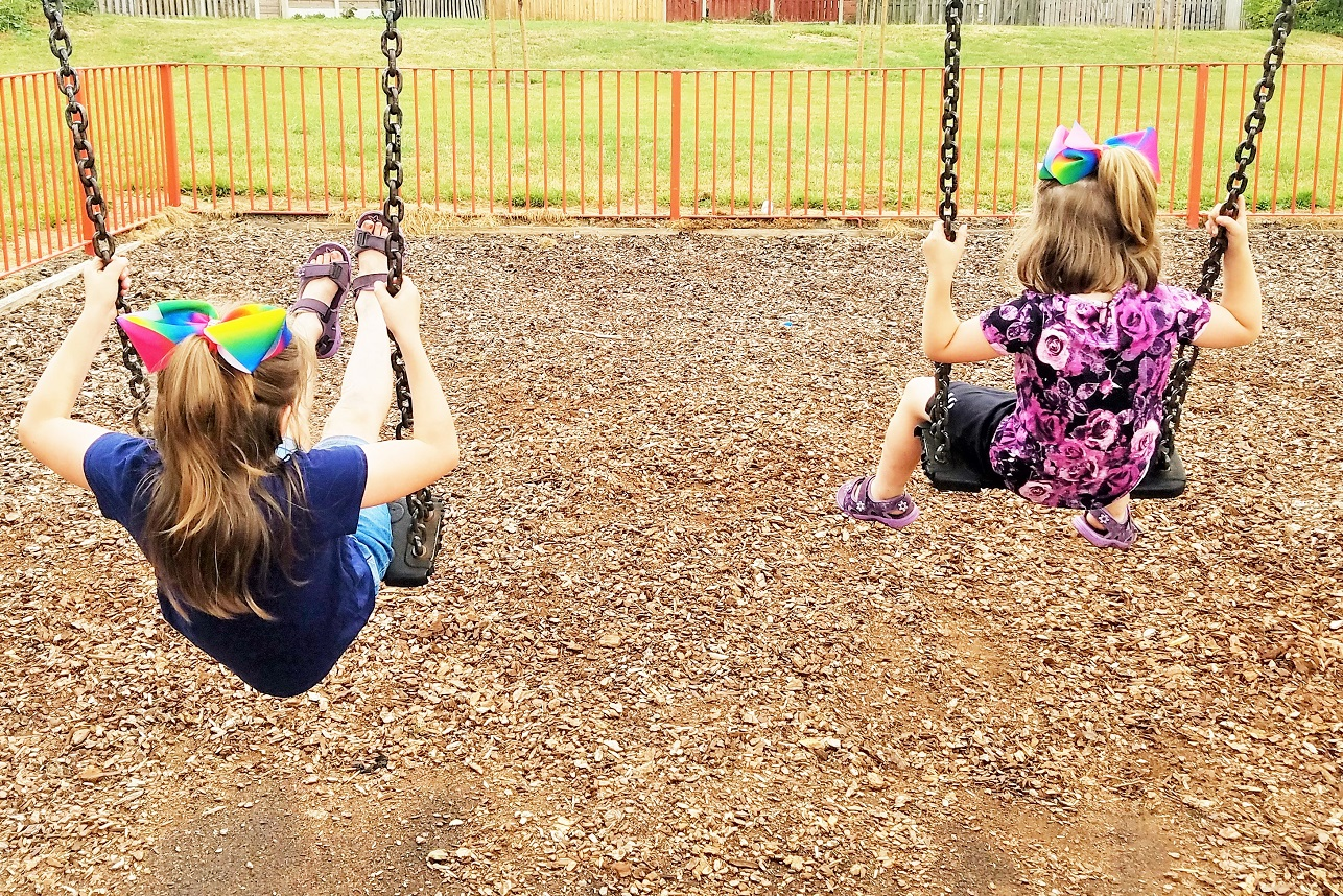 Empathy breeds love and trust in parenting - two children playing on the swings