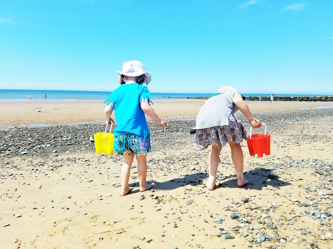 "Empty threats like ""we're going home"" trigger power struggles with your kids. Use these 10 steps instead - two children walking along the beach with buckets"