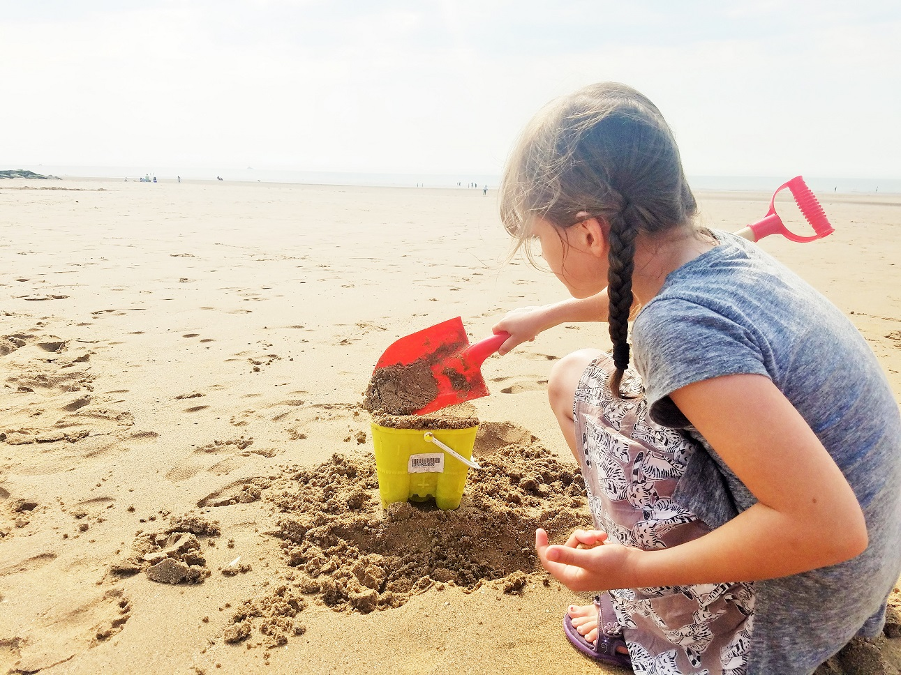 The kids are listening - negative labelling can be harmful to children - child digging a sandcastle