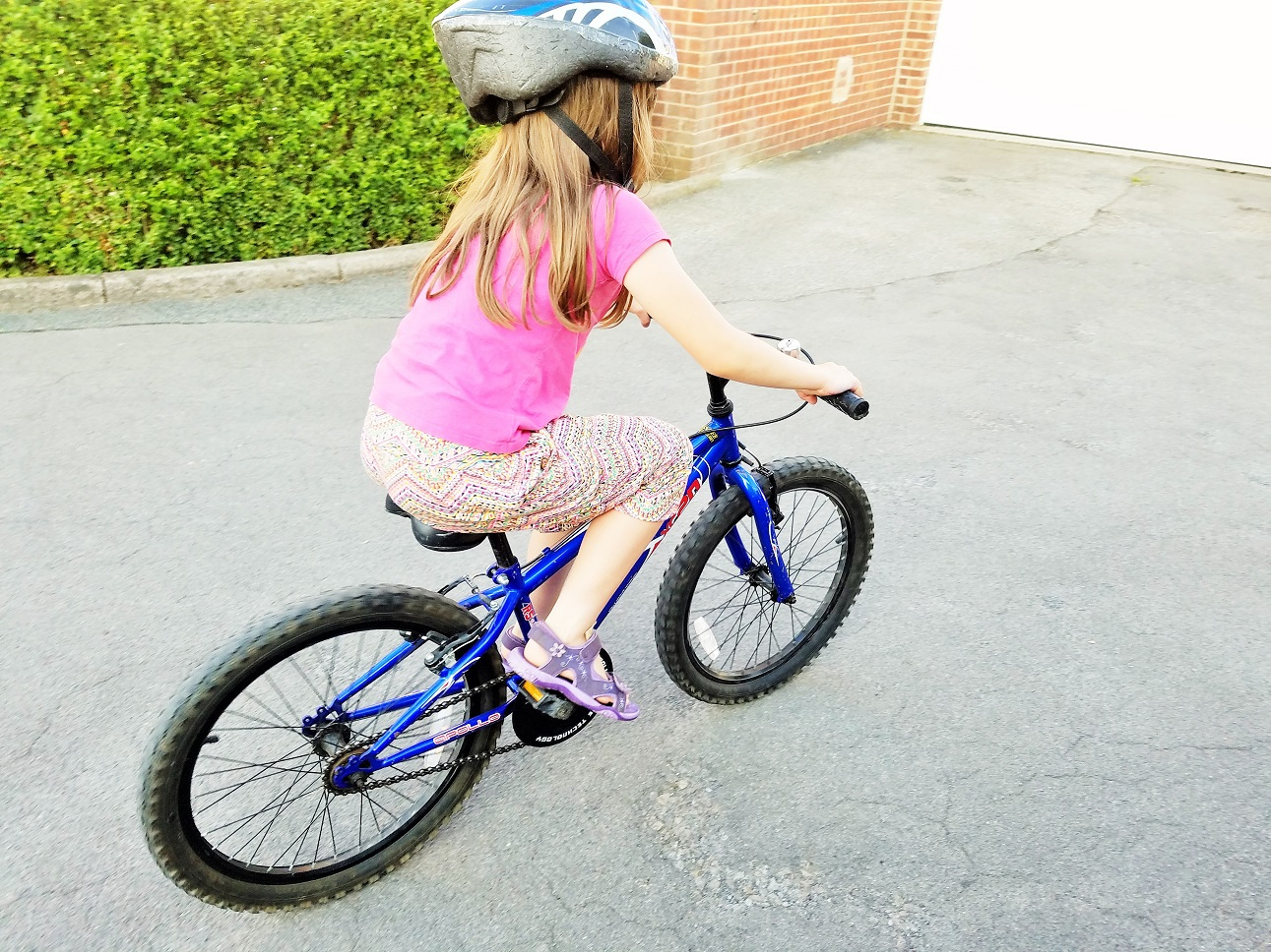 The problem with parenting advice - child riding a bike with helmet on