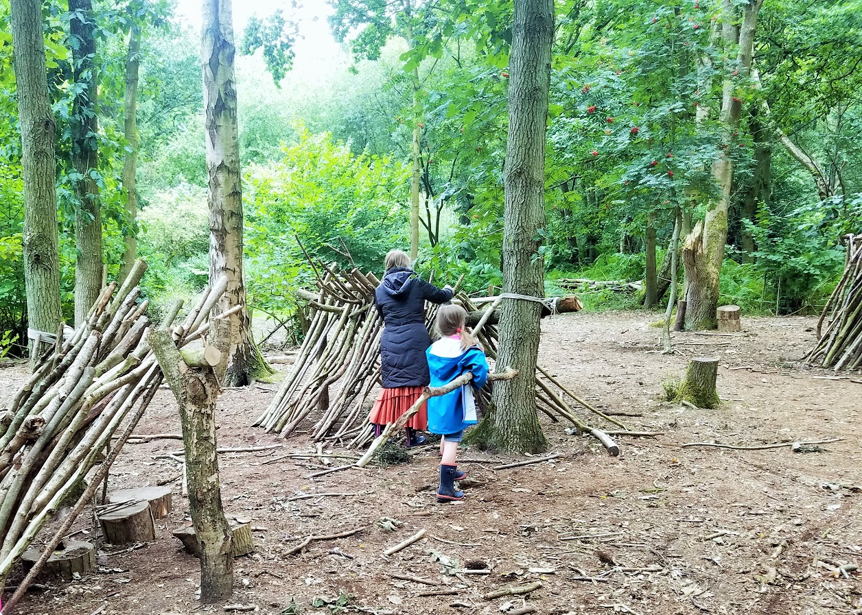 The big problem with parenting advice - mum helping child build den with sticks - BlogCrush Week 82