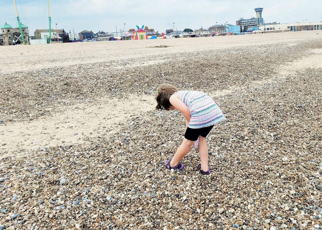 Parenting using praise as positive reinforcement - child collecting pebbles on the beach