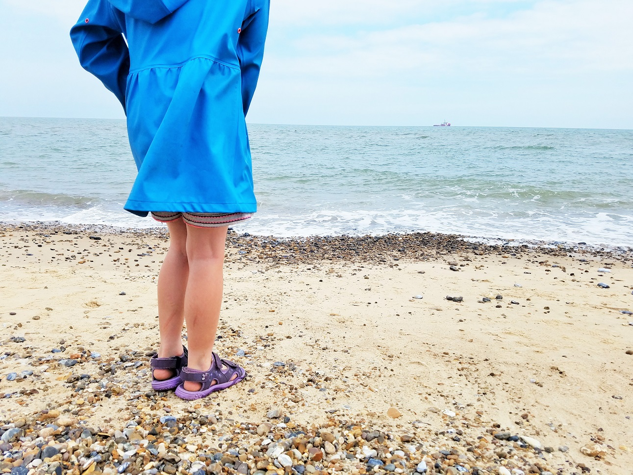 How to use positive praise to encourage good behaviour - child on the beach in a blue coat - BlogCrush Week 84