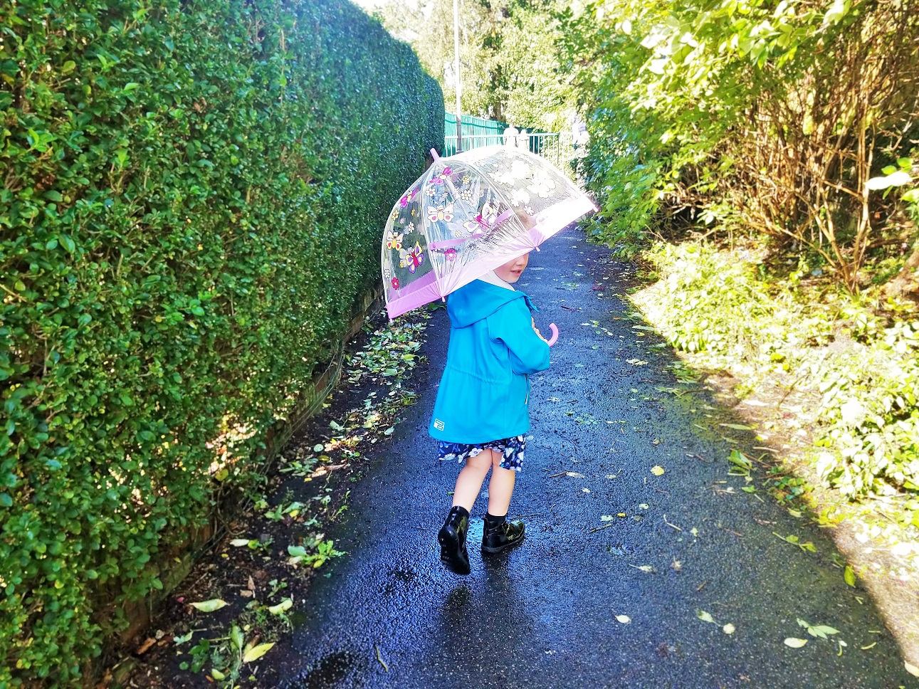 "10 Gentle Parenting Steps to try before saying ""We're going home"" - child in a blue coat holding an umbrella - blogcrush week 87"
