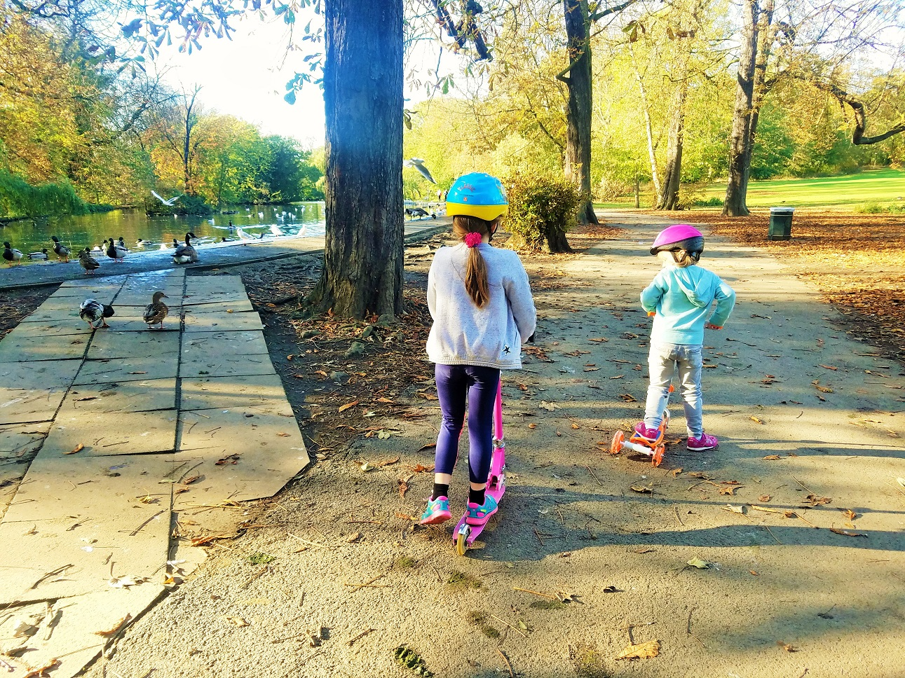 11 Hidden Issues that My be Affecting Your Child's Behaviour - two children on scooters by a lake - BlogCrush Week 90