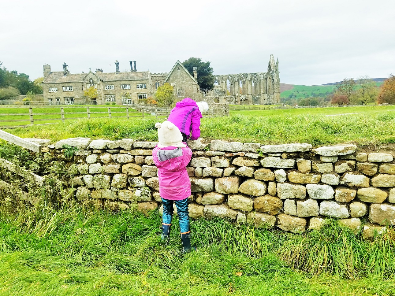 How to prepare little kids for big changes - sisters helping each other climb the wall at Bolton Abbey