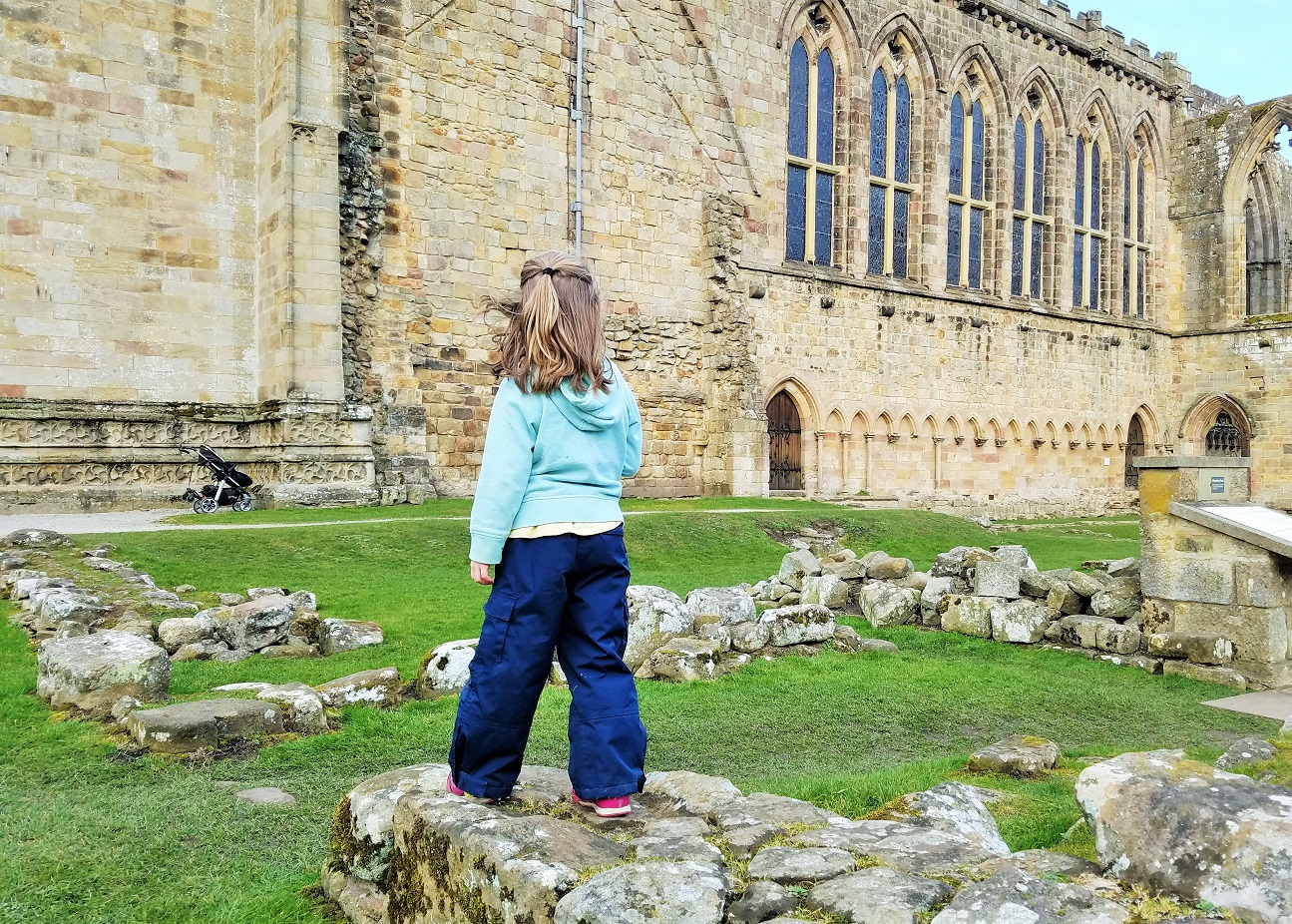 parenting myths that prop up mainstream parenting child in the grounds of a ruined church